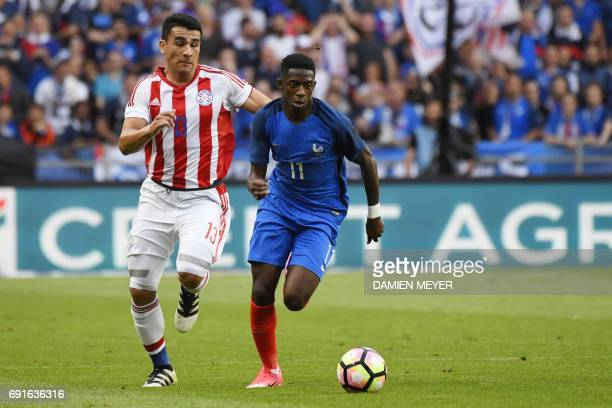 France's forward Ousmane Dembele vies with Paraguay's defender Junior Alonso during the friendly football match between France and Paraguay on June...
