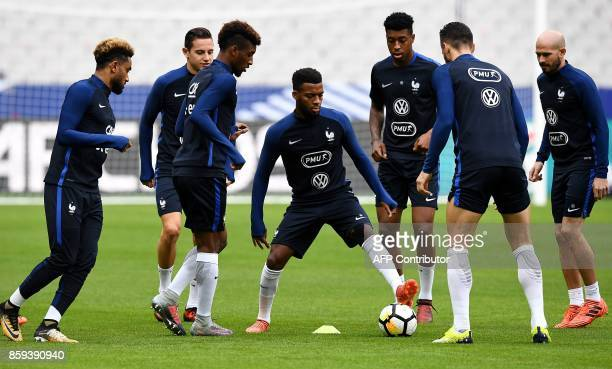France's forward Thomas Lemar controls the ball next to France's midfielder Presnel Kimpembe France's defender Jordan Amavi France's defender Florian...