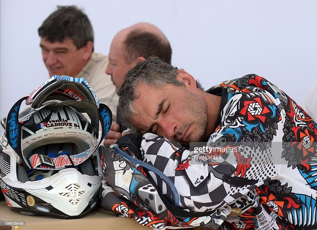 France's Francis Gadioux sleeps during the breakfast before the Stage 5 of the Dakar 2013 between Nazca and Arequipa, Peru, on January 9, 2013. The rally takes place in Peru, Argentina and Chile from January 5 to 20. AFP PHOTO / FRANCK FIFE