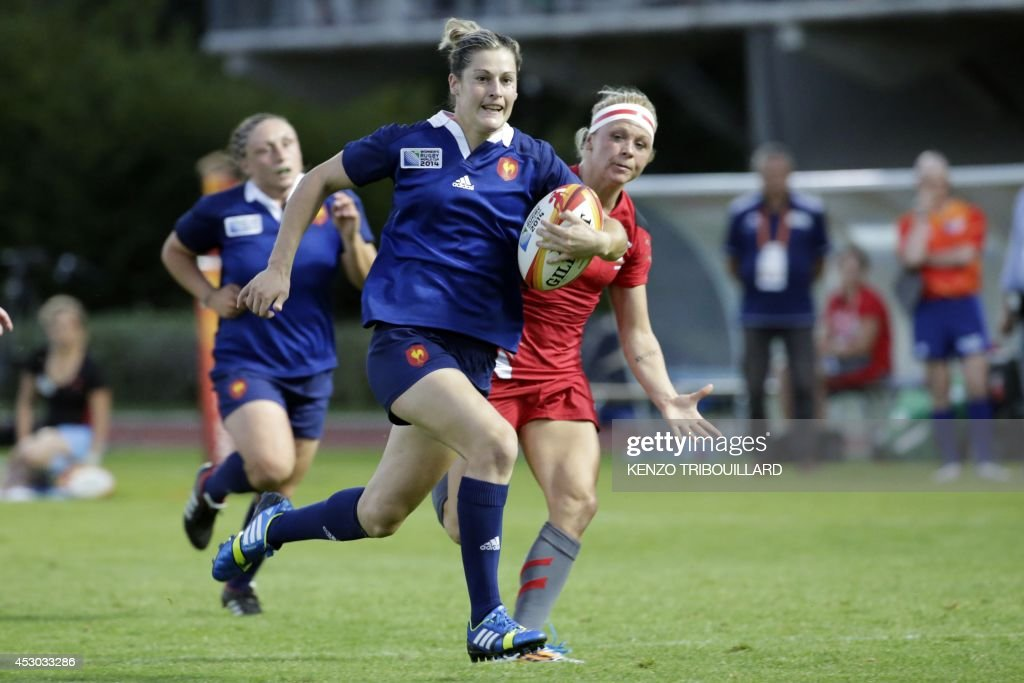 France's fullback Caroline Ladagnous (C) runs with the ball during the IRB Women's Rugby World Cup match between France and Wales at the French Rugby Federation headquarters in Marcoussis, near Paris, on August 1, 2014. AFP PHOTO / KENZO TRIBOUILLARD