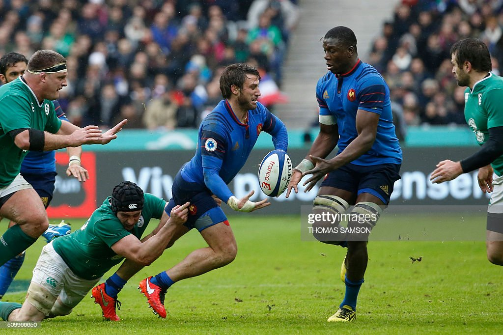 France's fullback Maxime Medard (C) is tackled during the Six Nations international rugby union match between France and Ireland at the Stade de France Stadium in Saint-Denis, north of Paris, on February 13, 2016. AFP PHOTO / THOMAS SAMSON / AFP / THOMAS SAMSON