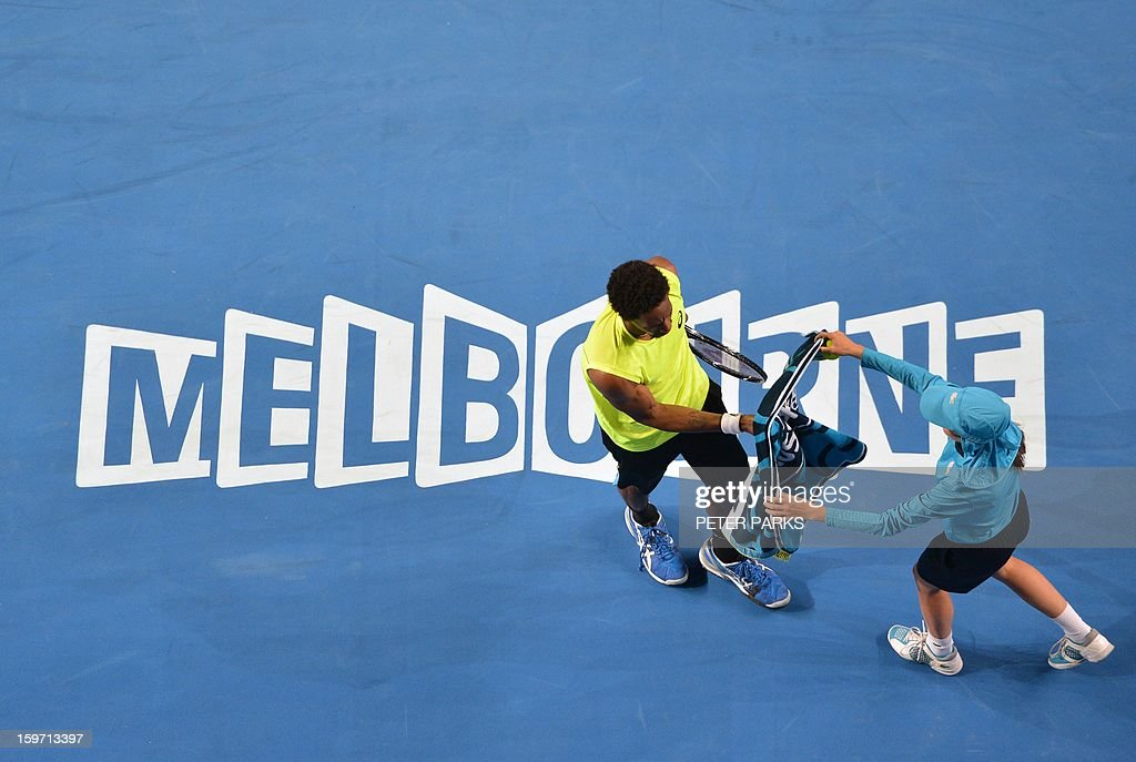 France's Gael Monfils takes a towel from a ballboy in his men's singles match against France's Gilles Simon on day six of the Australian Open tennis tournament in Melbourne on January 19, 2013.