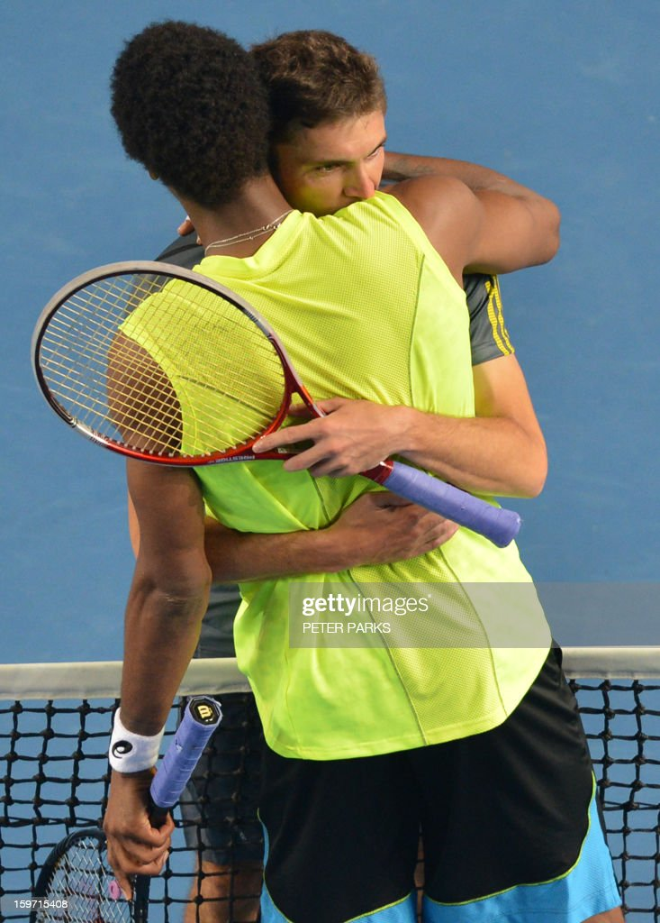 France's Gilles Simon (R) embraces compatriot Gael Monfils after victory in his men's singles match on the sixth day of the Australian Open tennis tournament in Melbourne early January 20, 2013.