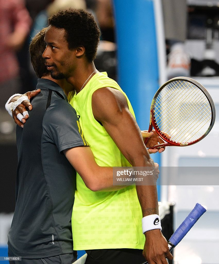 France's Gilles Simon (L) hugs France's Gael Monfils after his victory during their men's singles match on day six of the Australian Open tennis tournament in Melbourne early on January 20, 2013.