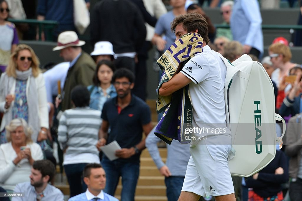 France's Gilles Simon leaves the court after being beaten by Bulgaria's Grigor Dimitrov during their men's singles second round match on the fourth day of the 2016 Wimbledon Championships at The All England Lawn Tennis Club in Wimbledon, southwest London, on June 30, 2016. / AFP / GLYN
