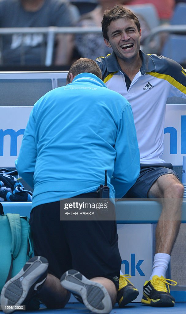 France's Gilles Simon (R) receives treatment during his men's singles match against Britain's Andy Murray on the eighth day of the Australian Open tennis tournament in Melbourne on January 21, 2013.