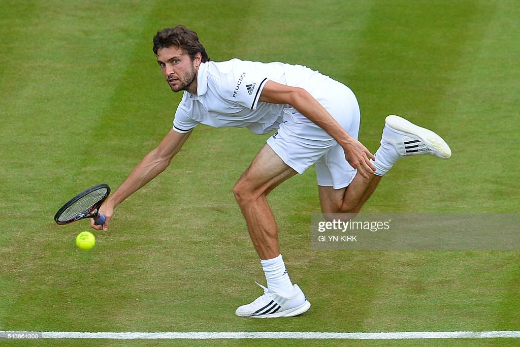TOPSHOT - France's Gilles Simon returns against Bulgaria's Grigor Dimitrov during their men's singles second round match on the fourth day of the 2016 Wimbledon Championships at The All England Lawn Tennis Club in Wimbledon, southwest London, on June 30, 2016. / AFP / GLYN