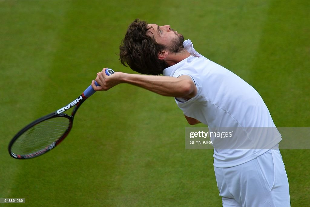 France's Gilles Simon serves against Bulgaria's Grigor Dimitrov during their men's singles second round match on the fourth day of the 2016 Wimbledon Championships at The All England Lawn Tennis Club in Wimbledon, southwest London, on June 30, 2016. / AFP / GLYN