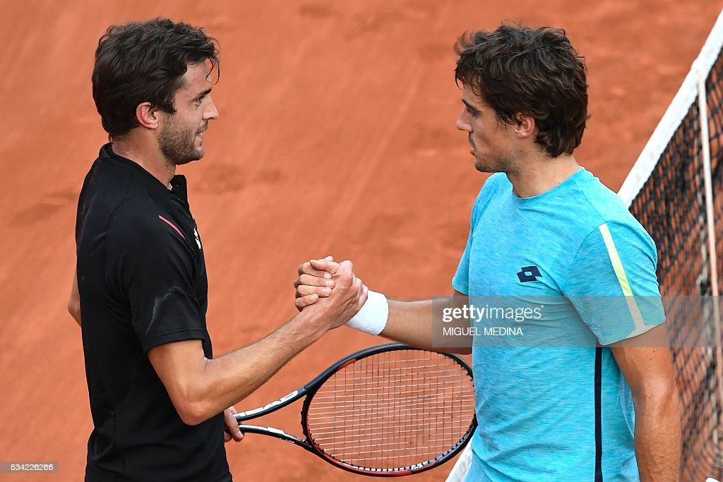 France's Gilles Simon (L) shakes hands with Argentina's Guido Pella after winning their men's second round match at the Roland Garros 2016 French Tennis Open in Paris on May 25, 2016. / AFP / MIGUEL