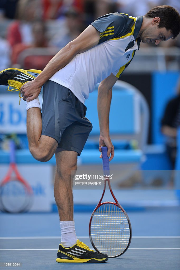 France's Gilles Simon stretches during his men's singles match against Britain's Andy Murray on the eighth day of the Australian Open tennis tournament in Melbourne on January 21, 2013.