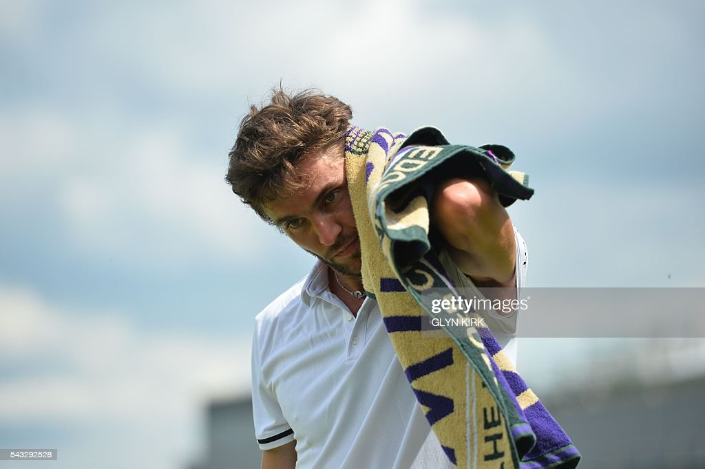France's Gilles Simon wipes his head between games against Serbia's Janko Tipsarevic during their men's singles first round match on the first day of the 2016 Wimbledon Championships at The All England Lawn Tennis Club in Wimbledon, southwest London, on June 27, 2016. / AFP / GLYN