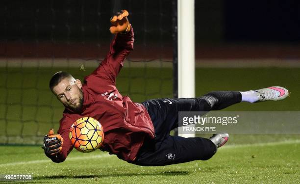 France's goalkeaper Benoit Costil dives to catch a ball during a training session in ClairefontaineenYvelines on November 10 2015 ahead of a friendly...