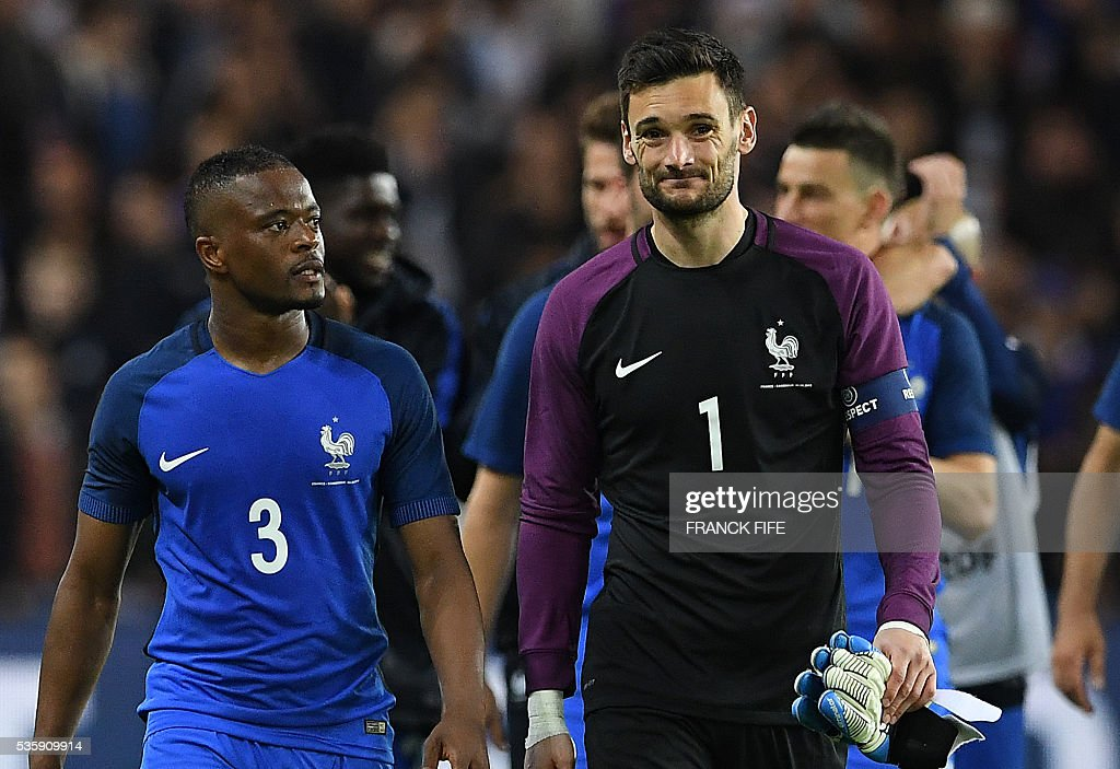 France's goalkeeper Hugo Lloris (R) and France's defender Patrice Evra react after winning the friendly football match between France and Cameroon, at the Beaujoire Stadium in Nantes, western France, on May 30, 2016. / AFP / FRANCK