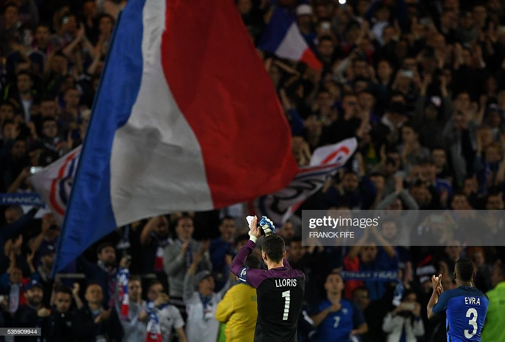 France's goalkeeper Hugo Lloris (L) and France's defender Patrice Evra react after winning the friendly football match between France and Cameroon, at the Beaujoire Stadium in Nantes, western France, on May 30, 2016. / AFP / FRANCK
