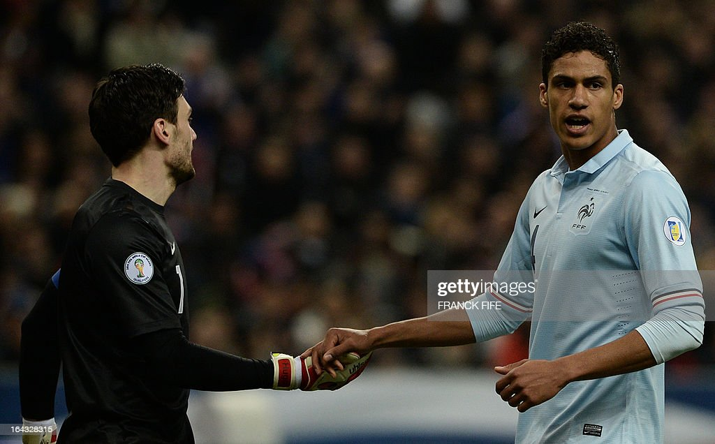 France's goalkeeper Hugo Lloris (L) shakes hands with France's defender Raphael Varane during the WC2014 qualifying football match France vs Georgia, on March 22, 2013 at the Stade de France in Saint-Denis, outside Paris.