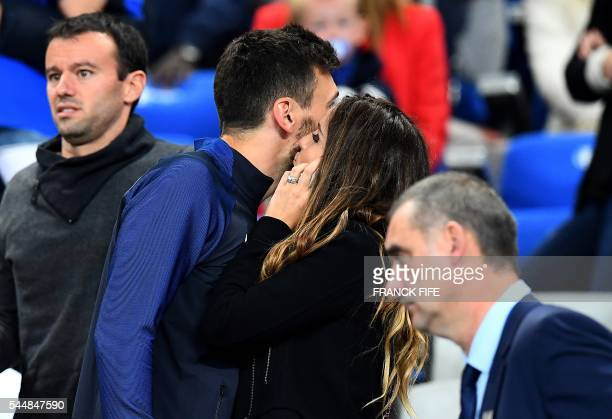 France's goalkeeper Hugo Lloris speaks with his wife Marine Lloris following the Euro 2016 quarterfinal football match between France and Iceland at...