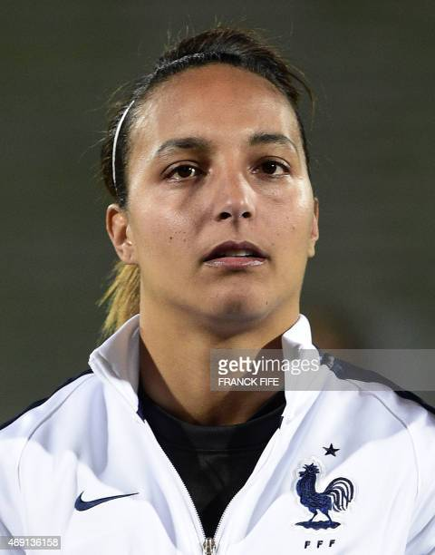 France's goalkeeper Sarah Bouhaddi poses during the French national anthem during the friendly football match France vs Canada on April 9 2015 at the...