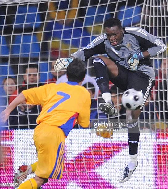 France's goalkeeper Steve Mandanda saves the ball in the front of Romania's Florentin Petre during their World Cup 2010 qualifying football match on...