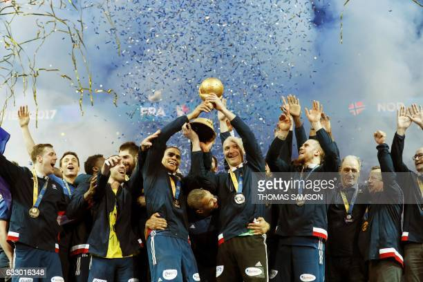 TOPSHOT France's goalkeeper Thierry Omeyer and France's centre back Daniel Narcisse hold thwe winner's trophy between France's head coach Didier...