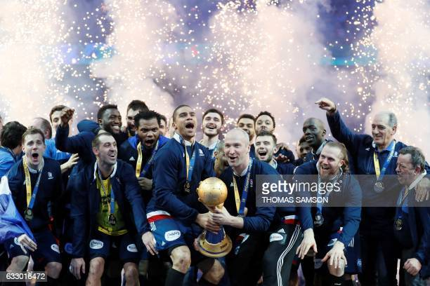 TOPSHOT France's goalkeeper Thierry Omeyer and France's centre back Daniel Narcisse hold thwe winner's trophy as France's teammates and staff...