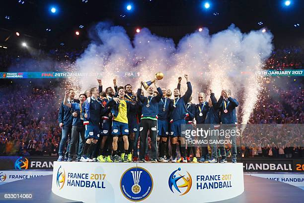 France's goalkeeper Thierry Omeyer holds the winner's trophy as France's teammates and staff celebrate winning the 25th IHF Men's World Championship...