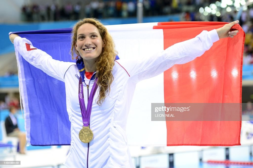 France's gold medalist Camille Muffat poses with a flag on the podium after winning the women's 400m freestyle swimming event at the London 2012...