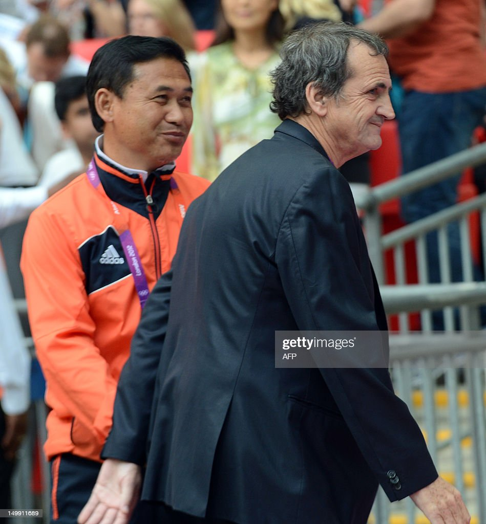 France's head coach Bruno Bini (R) greets Japan's head coach Norio Sasaki (L) prior to the 2012 London Olympics women's football semi final match between Japan and France at the Wembley stadium in London August 6, 2012. Japan beat France 2-1.