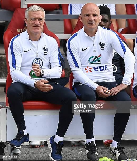 France's head coach Didier Deschamps and assistant coach Guy Stephan sit on a bench as they watch the friendly football match between French national...