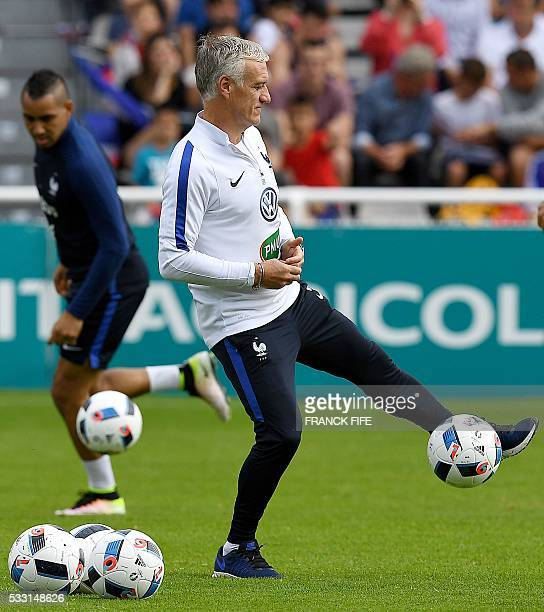 France's head coach Didier Deschamps controls the ball during a warmup with his team ahead of a friendly match between French national football team...