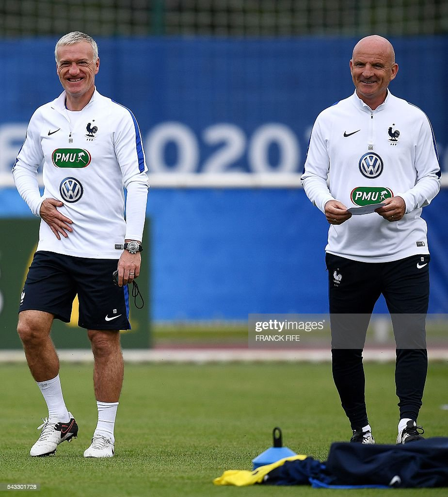 France's head coach Didier Deschamps (L) jokes with France's assistant coach Guy Stephan during a training session in Clairefontaine-en-Yvelines, southwest of Paris, on June 6, 2016, during the Euro 2016 football tournament. / AFP / FRANCK