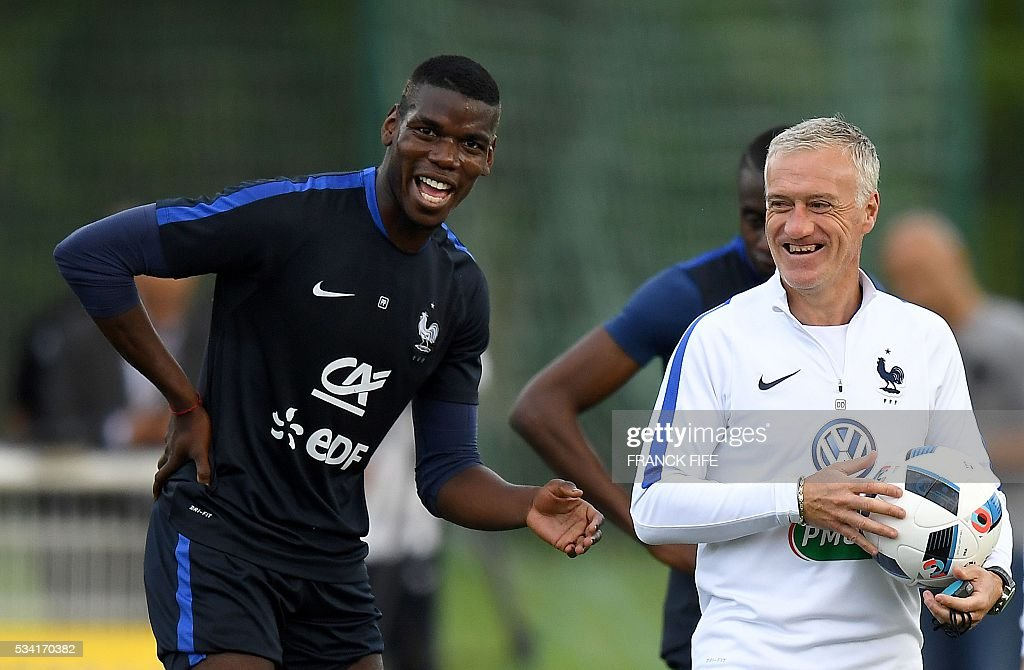 France's head coach Didier Deschamps (R) jokes with France's midfielder Paul Pogba (L) at the end of a training session in Clairefontaine as part of the team's preparation for the upcoming Euro 2016 European football championships, on May 25, 2016. / AFP / FRANCK