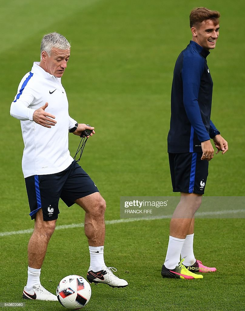 France's head coach Didier Deschamps (L) reacts behind France's forward Antoine Griezmann during a training session in Clairefontaine-en-Yvelines, southwest of Paris, on June 29, 2016, during the Euro 2016 football tournament. / AFP / FRANCK