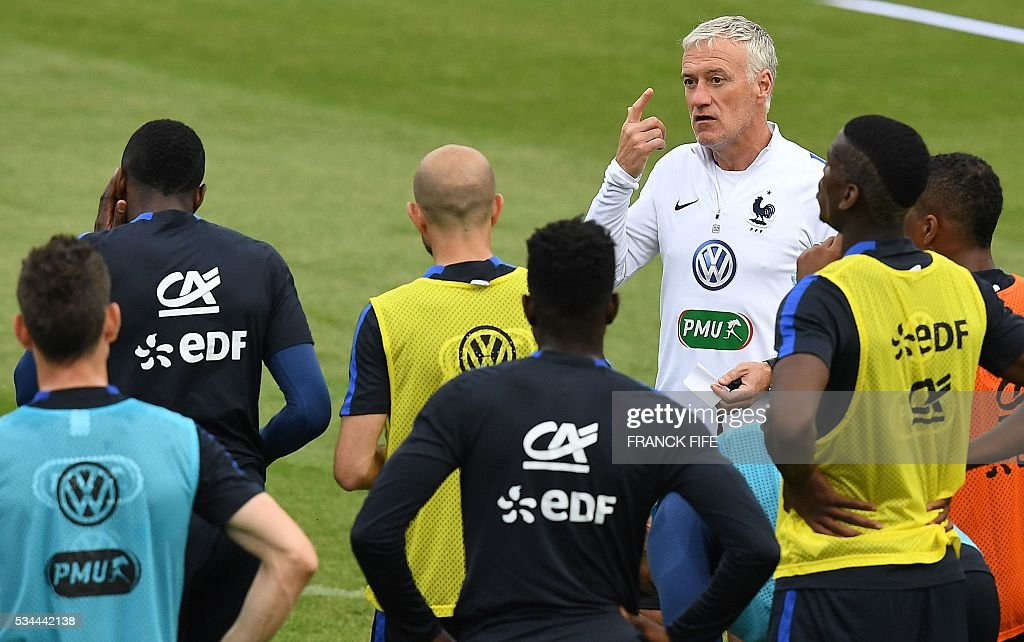 France's head coach Didier Deschamps (R) speaks to his players during a training session in Clairefontaine en Yvelines on May 26, 2016, as part of the team's preparation for the upcoming Euro 2016 European football championships. / AFP / FRANCK
