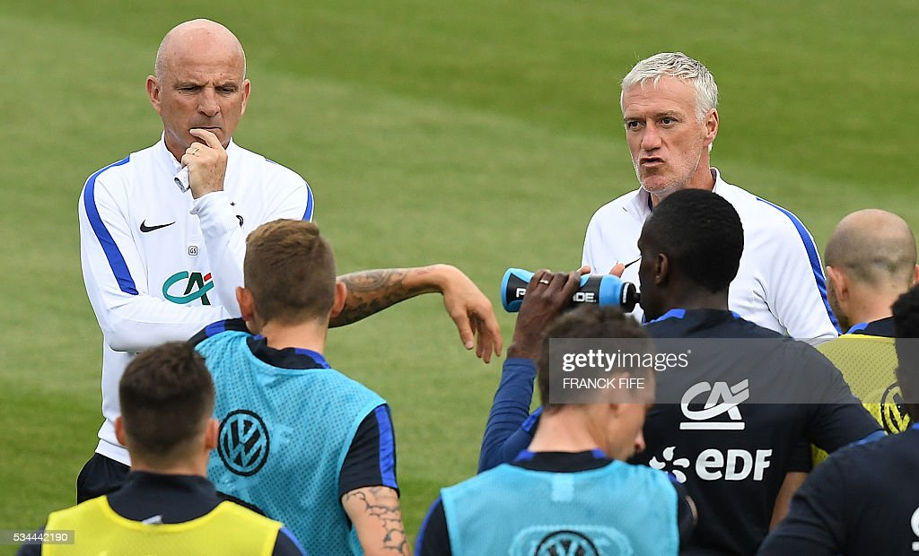 France's head coach Didier Deschamps (R) speaks to his players next to assistant coach Guy Stephan (L) during a training session in Clairefontaine en Yvelines on May 26, 2016, as part of the team's preparation for the upcoming Euro 2016 European football championships. / AFP / FRANCK