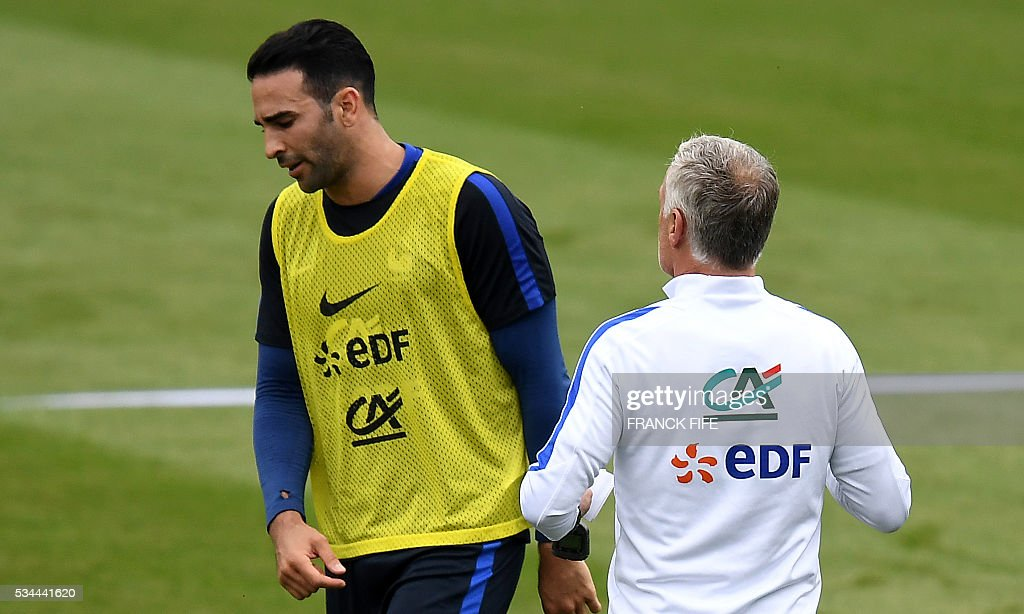 France's head coach Didier Deschamps (R) speaks with defender Adil Rami at the end of a training session in Clairefontaine en Yvelines on May 26, 2016, as part of the team's preparation for the upcoming Euro 2016 European football championships. / AFP / FRANCK