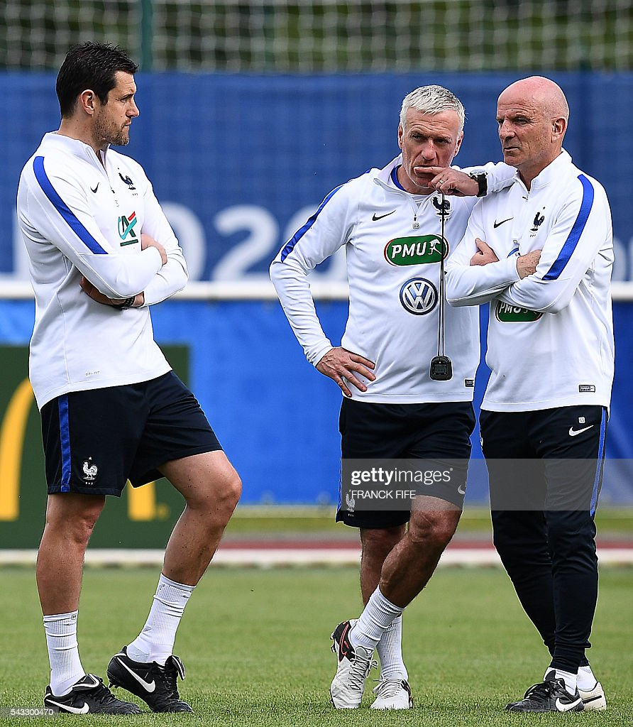 France's head coach Didier Deschamps (C) speaks with France's assistant coach Guy Stephan next to France's goalkeeper coach Franck Raviot take part in a training session in Clairefontaine-en-Yvelines, southwest of Paris, on June 6, 2016, during the Euro 2016 football tournament. / AFP / FRANCK