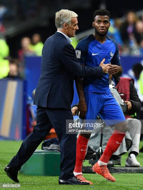 France's head coach Didier Deschamps speaks with France's forward Thomas Lemar a he leaves the pitch during the FIFA World Cup 2018 qualification...