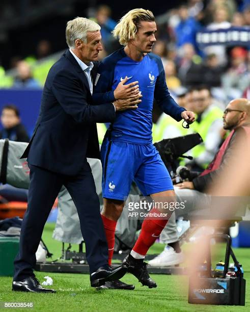 France's head coach Didier Deschamps speaks with France's forward Antoine Griezmann as he leaves the pitch during the FIFA World Cup 2018...