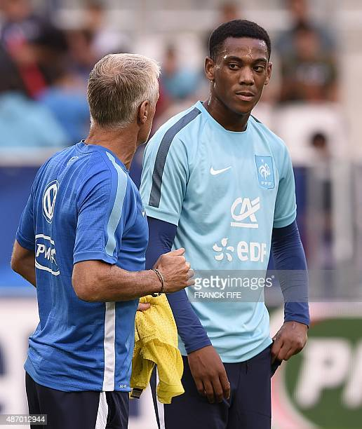France's head coach Didier Deschamps speaks with France's forward Anthony Martial at the end of training sesssion on September 5 2015 at the stadium...