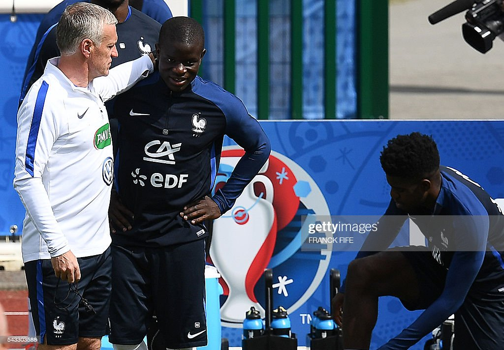 France's head coach Didier Deschamps (L) speaks with France's midfielder N'Golo Kante (2L) during a training session in Clairefontaine-en-Yvelines, southwest of Paris, on June 6, 2016, during the Euro 2016 football tournament. / AFP / FRANCK