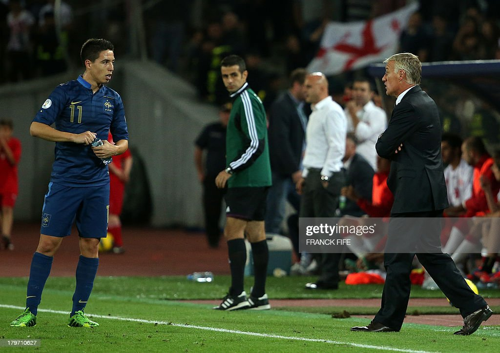 France's head coach Didier Deschamps (R) speaks with midfielder Samir Nasri during the FIFA World Cup 2014 qualifying football match Georgia vs France on September 6 2013 at the Boris Paichadze stadium in Tbilisi.