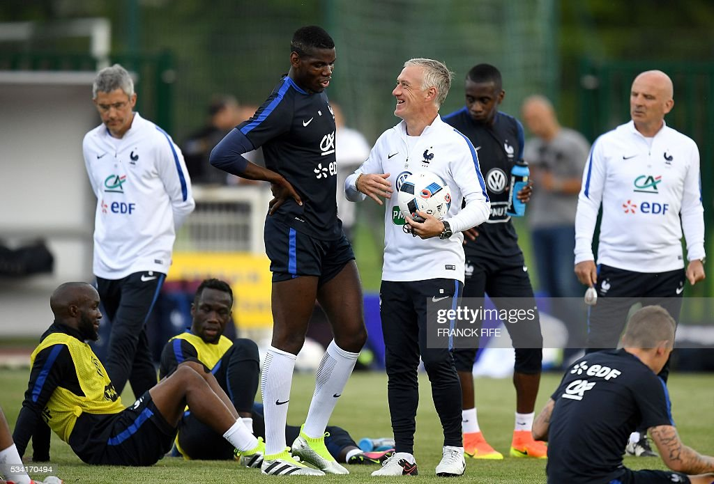 France's head coach Didier Deschamps (R) talks with France's midfielder Paul Pogba (L) at the end of a training session in Clairefontaine as part of the team's preparation for the upcoming Euro 2016 European football championships, on May 25, 2016. / AFP / FRANCK
