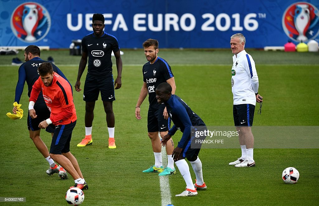 France's head coach Didier Deschamps (L) watches his players during a training session in Clairefontaine-en-Yvelines, southwest of Paris, on June 6, 2016, during the Euro 2016 football tournament. / AFP / FRANCK
