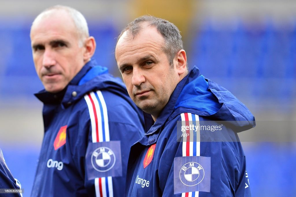 France's head coach Philippe Saint-Andre and assistant coach Patrice Lagisquet (L) look at their players during the captain's run on the eve of the Six Nations International Rugby Union match between Italy and France at the Olympic Stadium in Rome on February 2, 2013. AFP PHOTO / GABRIEL BOUYS