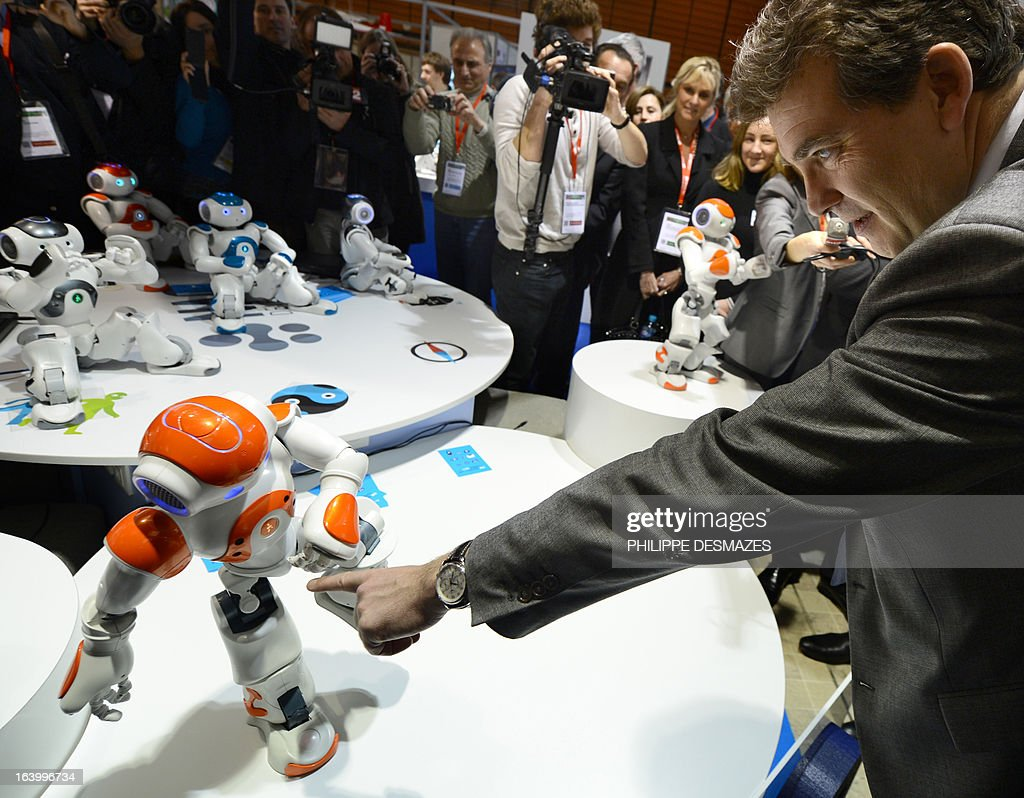 France's Industrial Renewal minister Arnaud Montebourg plays on March 19, 2013 with a NAO robot as he visits the Innorobo 2013 European summit in Lyon, southeastern France.