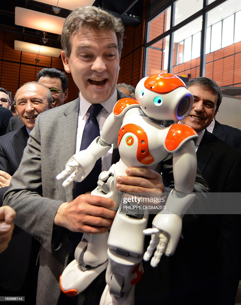 France's Industrial Renewal minister Arnaud Montebourg plays on March 19, 2013 with a NAO robot as he visits the Innorobo 2013 European summit in Lyon, southeastern France. Background, Lyon's mayor Gerard Collomb.