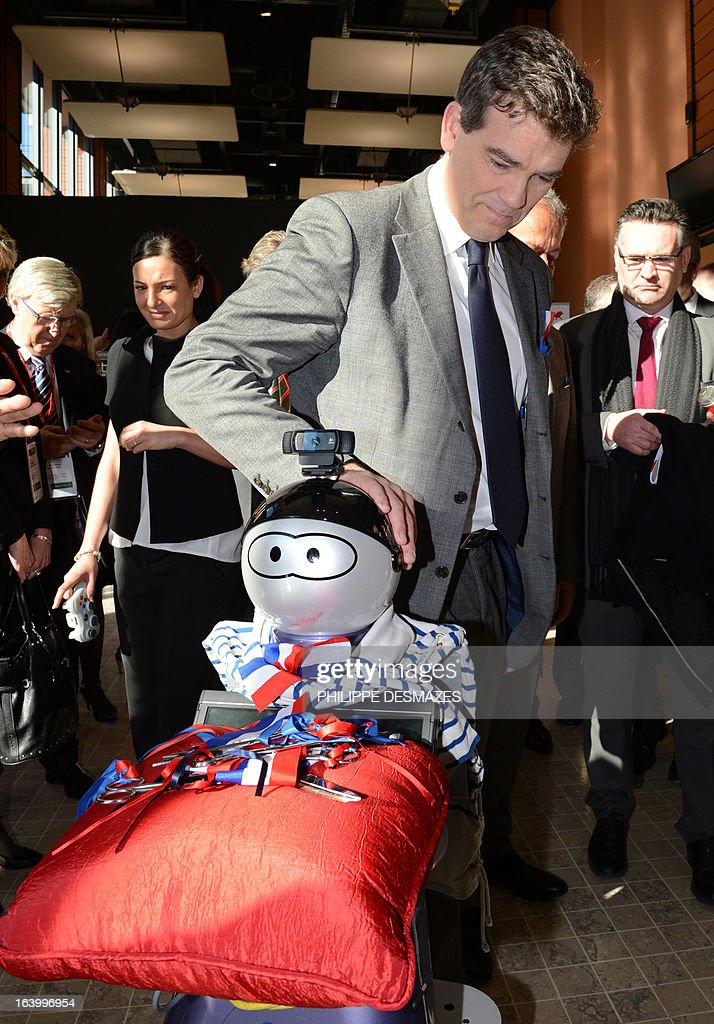 France's Industrial Renewal minister Arnaud Montebourg touches on March 19, 2013 a Kompai robot before the inaugural ceremony of the Innorobo 2013 European summit in Lyon, southeastern France. AFP PHOTO/PHILIPPE DESMAZES