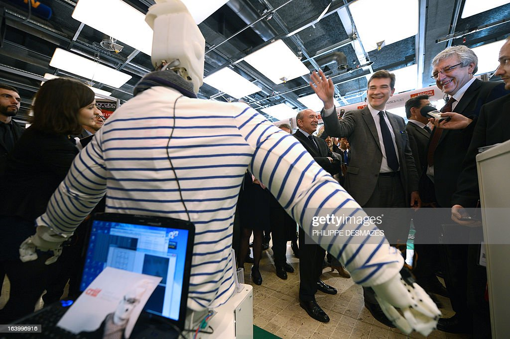 France's Industrial Renewal minister Arnaud Montebourg (C) waves on March 19, 2013 to SAMI, a humanoid robot, as he visits the Innorobo 2013 European summit in Lyon, southeastern France.