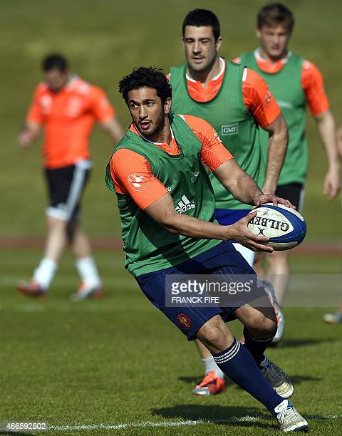 France's inside centre Maxime Mermoz runs with the ball during a training session in Marcoussis south of Paris on March 17 2015 ahead of the Six...