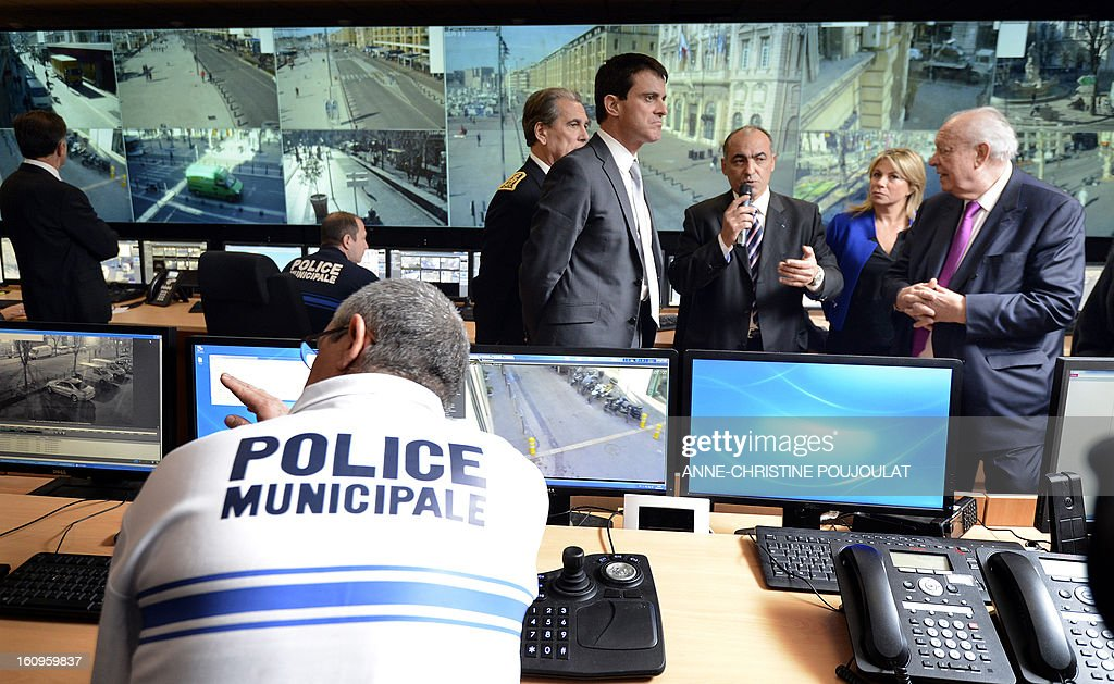France's Interior Minister Manuel Valls (4thR) listens to Marseille's mayor Jean-Claude Gaudin (R) visits the real-time protection video operating room during the inauguration of the Urban Supervision Centre (CSU) on February 8, 2013 in Marseille, southern France.